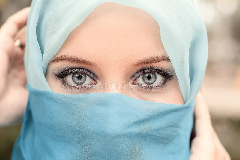 Pretty girl with beautiful big blue eyes, big eyelashes and eyebrows. Portrait of beautiful woman with blue eyes wearing blue sc royalty free stock photo