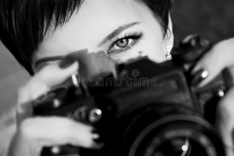 Pretty girl with beautiful eyes make pictures in a city park. Black and white photo stock photography