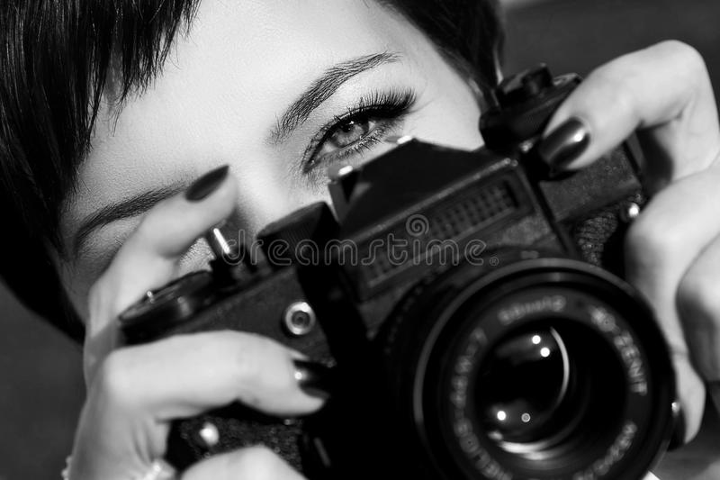 Pretty girl with beautiful eyes make pictures in a city park. Black and white photo royalty free stock photo