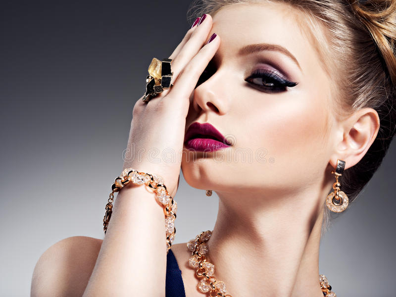 Pretty girl with beautiful face bright make-up and gold jewelry royalty free stock image
