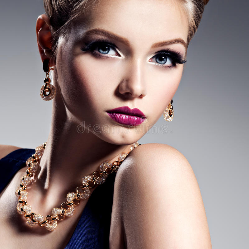 Pretty girl with beautiful gold jewelry and bright make-up. Posing at studio royalty free stock photo