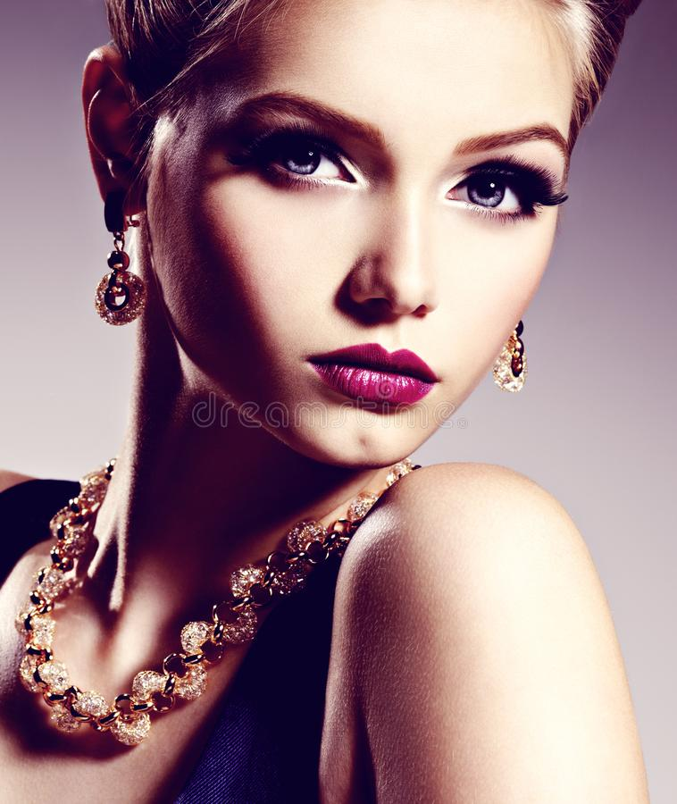 Pretty girl with beautiful gold jewelry and bright make-up. Posing at studio stock images