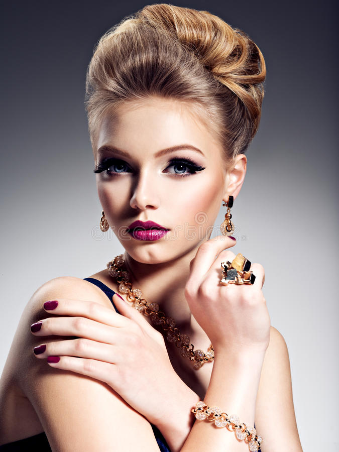 Pretty girl with beautiful hairstyle and gold jewelry, bright m royalty free stock images