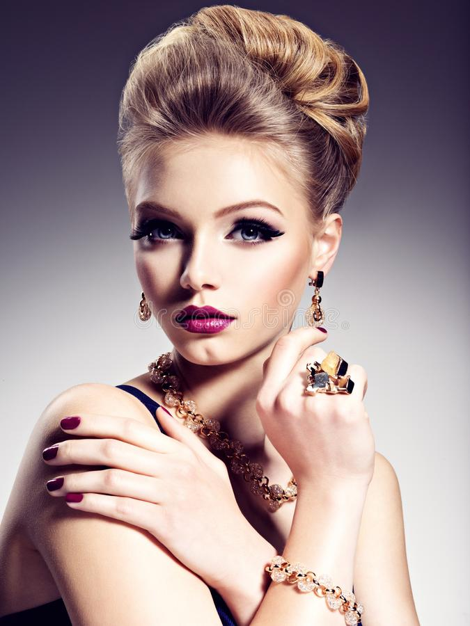 Pretty girl with beautiful hairstyle and gold jewelry, bright m stock photos