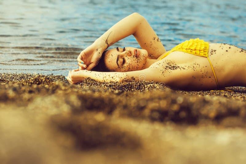 Pretty girl in yellow swimsuit sleeping on sea beach stock photo
