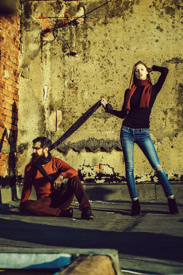 Girl keeps man on scarf. Pretty girl beautiful women keeps bearded men hipster with beard on scarf on sunny autumn day outdoors on roof on concrete wall royalty free stock photo