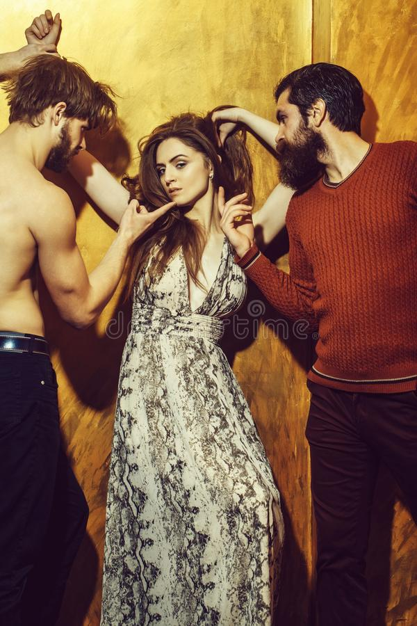 Pretty girl and two bearded men with beards. Pretty girl or beautiful women with long brunette hair in dress and two bearded men with beards, caucasian hipsters stock image
