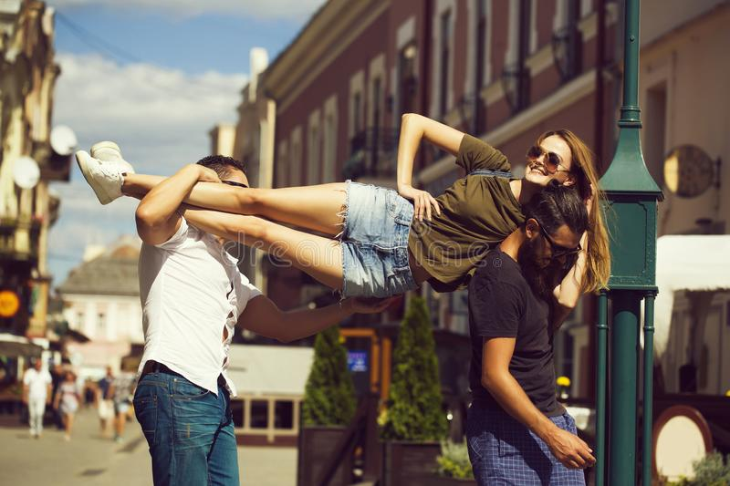 Pretty girl on shoulders of handsome men. Pretty girl or beautiful women in sunglasses and jean shorts on shoulders of handsome men on sunny summer day on urban royalty free stock photo