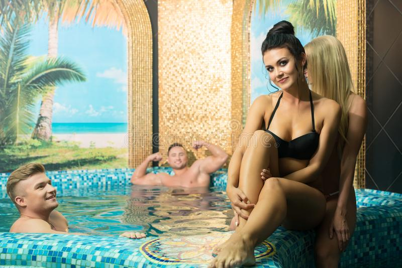 Happy young company in swimming pool in sauna royalty free stock photography
