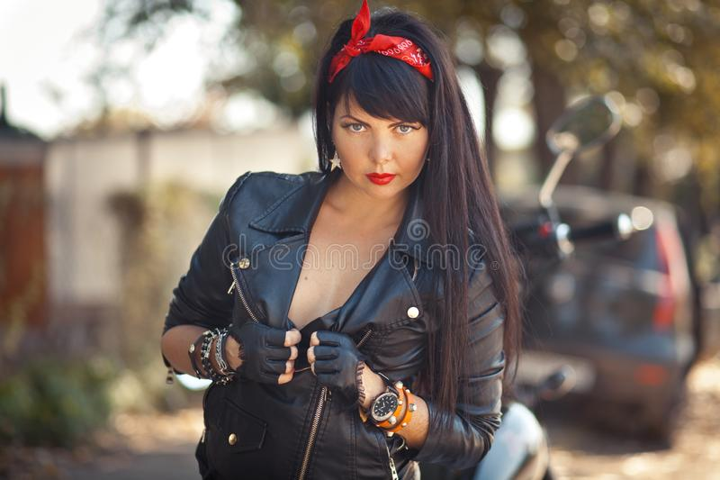 Pretty girl biker or cute woman with stylish, long hair wearing jeans sitting on floor at motorcycle royalty free stock image