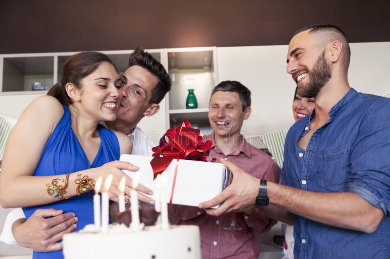 Pretty girl with birthday cake receiving the gift from his friends. In a modern apartment stock photos