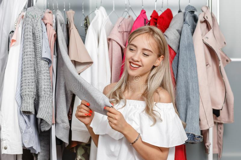 Pretty girl blogger stands on the background of clothes hanging on a hanger in the wardrobe and touches the sleeve of stock photos
