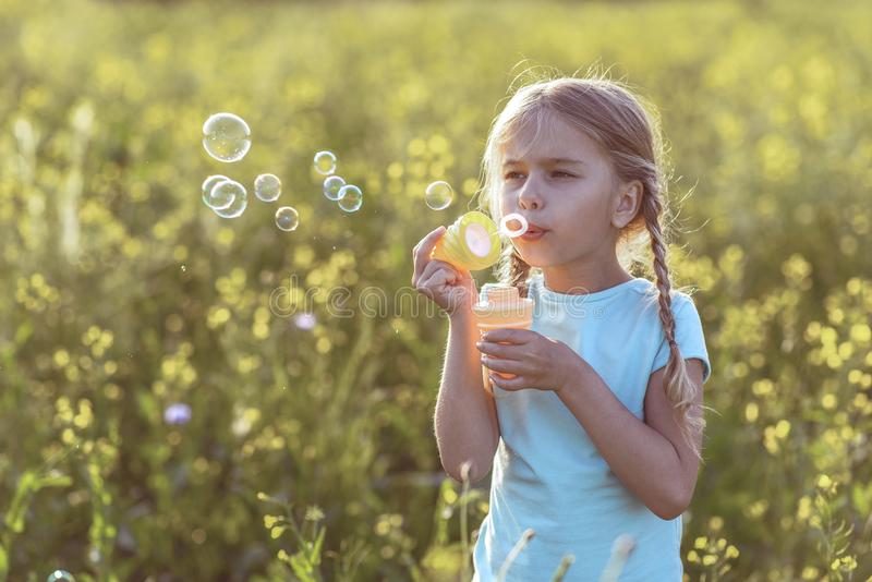 Pretty girl blowing bubbles on meadow stock photography