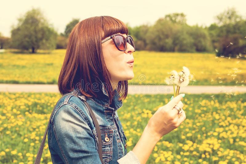 Pretty girl blowing dandelion in summer park. Green grass beautiful nature. stock images