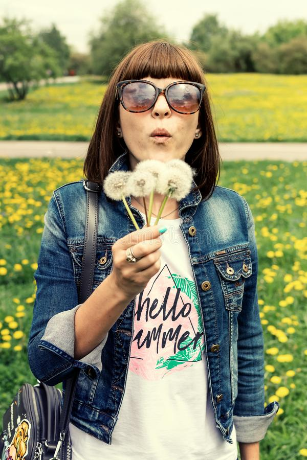Pretty girl blowing dandelion in summer park. Green grass beautiful nature. royalty free stock photography