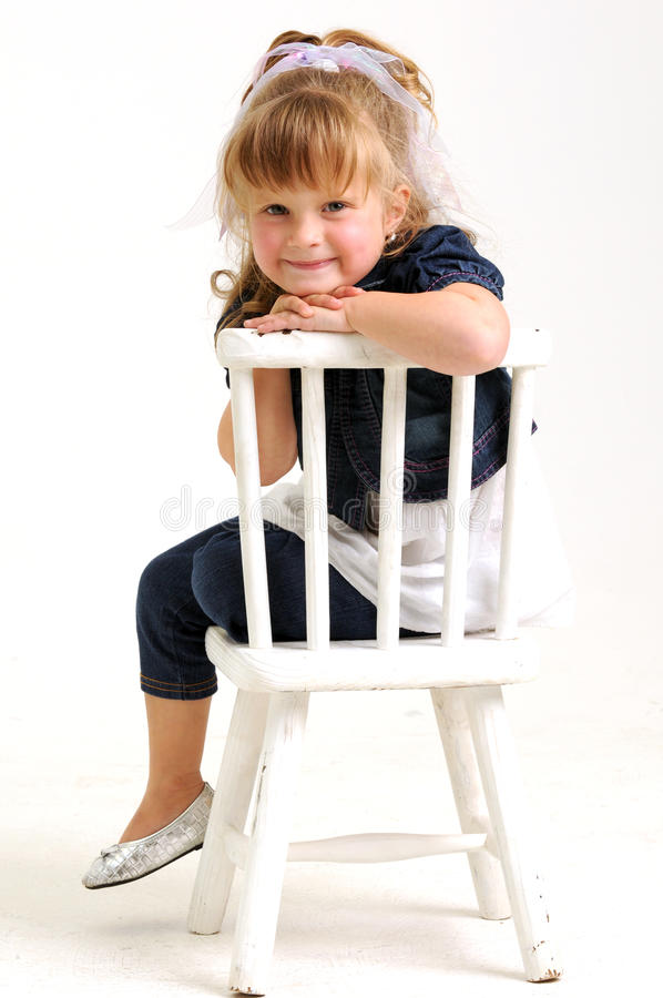 Pretty girl in blue dress sitting white chair stock photography