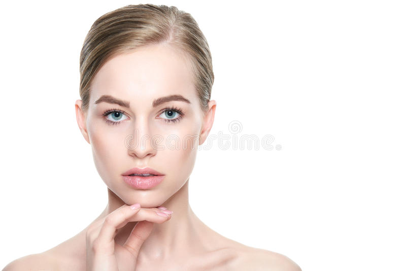 Pretty girl with blue eyes and blond hair, with naked shoulders, looking at camera.Model with light nude make-up, white background royalty free stock photo