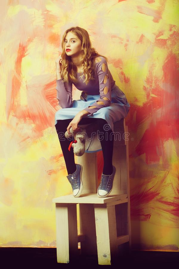 Pretty girl in blue skirt and sneakers with soft toy. Pretty girl or beautiful woman with blond curly hair in stylish blue skirt and sneakers with soft toy sits royalty free stock photos