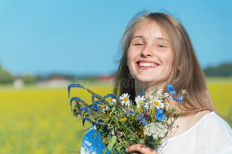 Pretty girl with a bouquet in the field royalty free stock photo