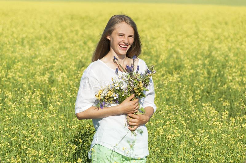 Pretty girl with a bouquet in the field stock photography