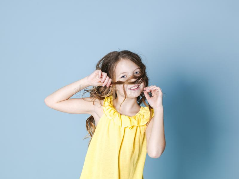 Pretty, happy girl with brunette hair with yellow top posing in front of blue background and making different facial expressions. Pretty girl with brunette hair royalty free stock image