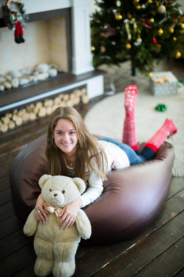 Pretty girl with cheerful smile and teddy bear. View from above on attractive girl lying on soft frameless chair and hugging with white teddy bear. Christmas eve royalty free stock image