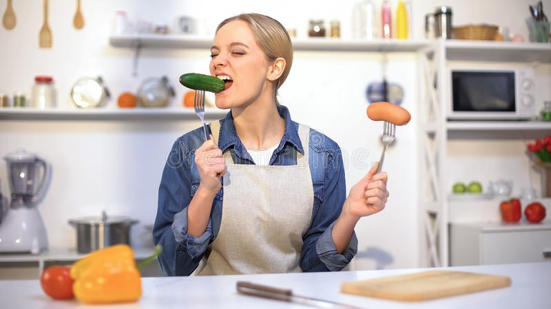 Pretty girl choosing cucumber instead sausage, low-calorie food vs carbohydrates stock image