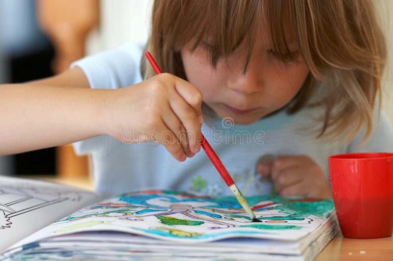 Pretty girl coloring a book. Preschool stock photography