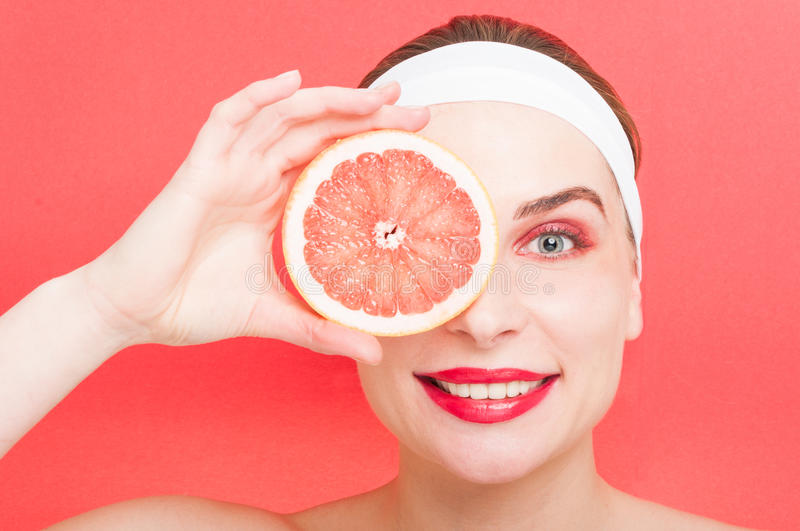 Pretty girl is covering her eye with grapefruit. Pretty girl is covering her eye with a slice of grapefruit as citrus food concept isolated on red background royalty free stock photography