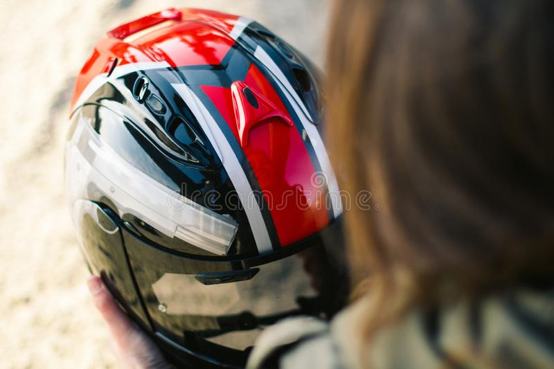 Pretty girl with custom motorcycle helmet. In hands with sunbright background stock photography