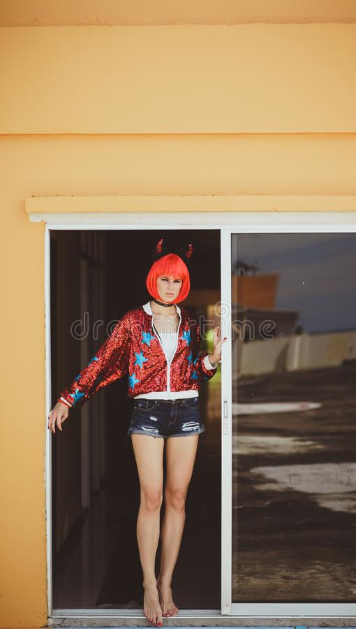Pretty girl in devil costume standing in a gloomy corridor by the window. Wears a red wig with horns, denim shorts and stock photography