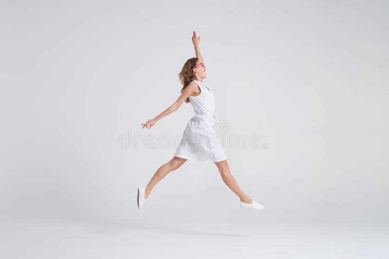 Pretty girl in dress jumping isolated over background royalty free stock image