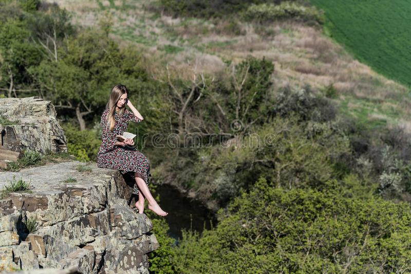 Pretty girl in dress reads book on rock in nature royalty free stock photography