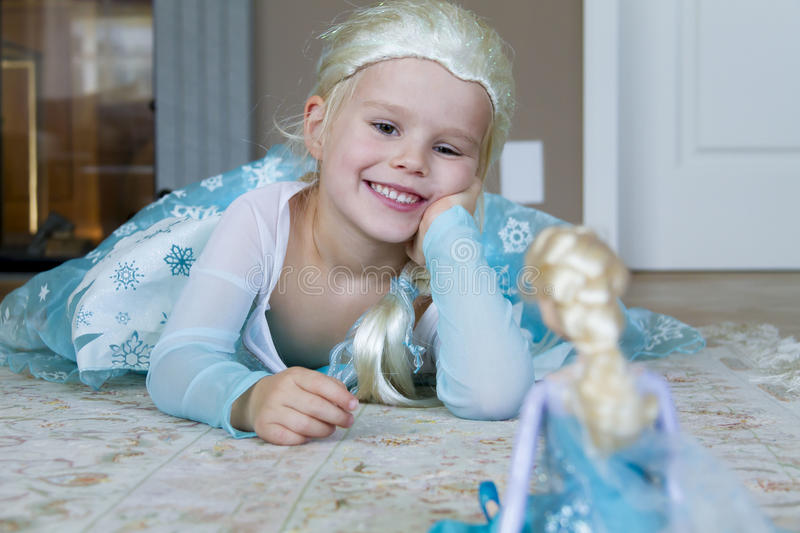 Pretty girl dressed as Disney Frozen Princess Elsa. Pretty blond girl dressed as Disney Frozen Princess Elsa playing with Elsa barbie doll. Cute little girl royalty free stock image