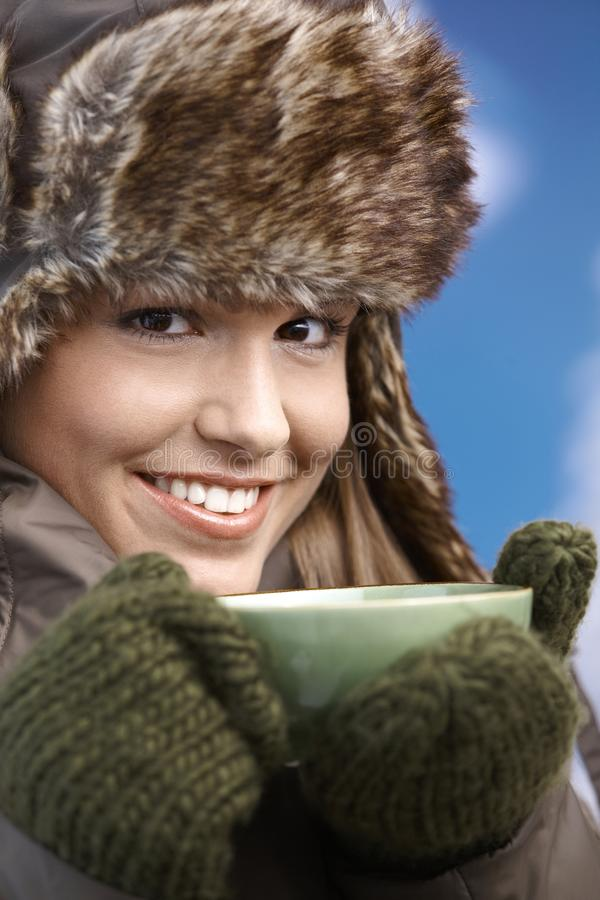 Pretty girl dressed up warm drinking tea smiling. Pretty young girl dressed up warm in coat, fur-hat and gloves, drinking hot tea, smiling royalty free stock image