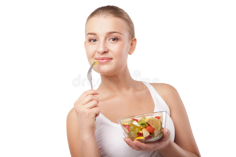 Pretty girl eating fruit salad isolated. Pretty girl eating fruit salad, healthy fresh breakfast, dieting and health care concept isolated royalty free stock images