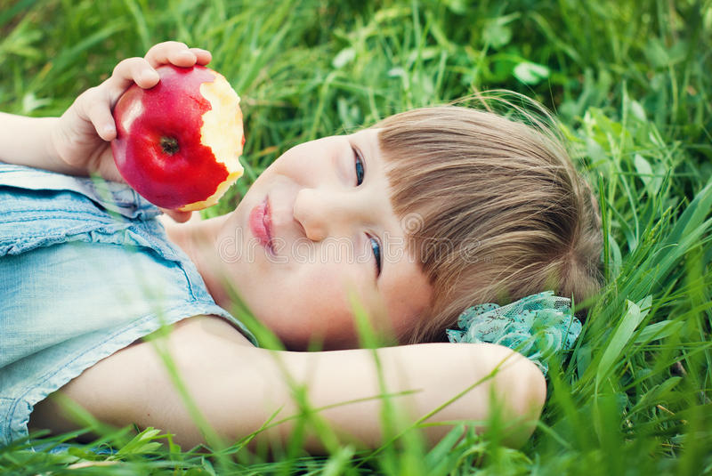 Pretty girl eating red apple on grassland. Happy kids concept. stock photos