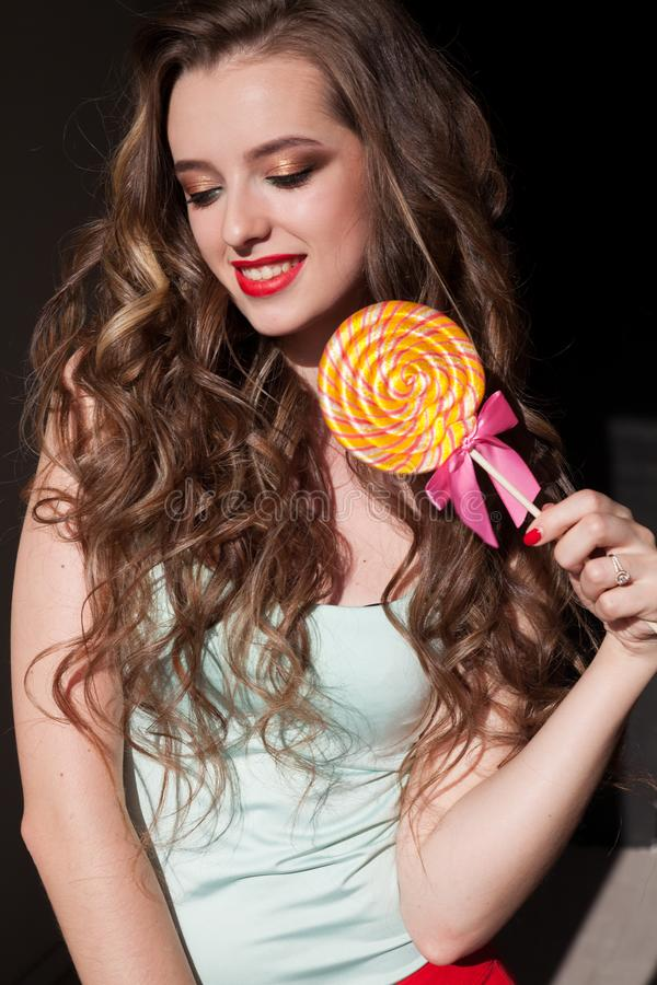 Pretty girl eats sweet candy lollipop candy stock image