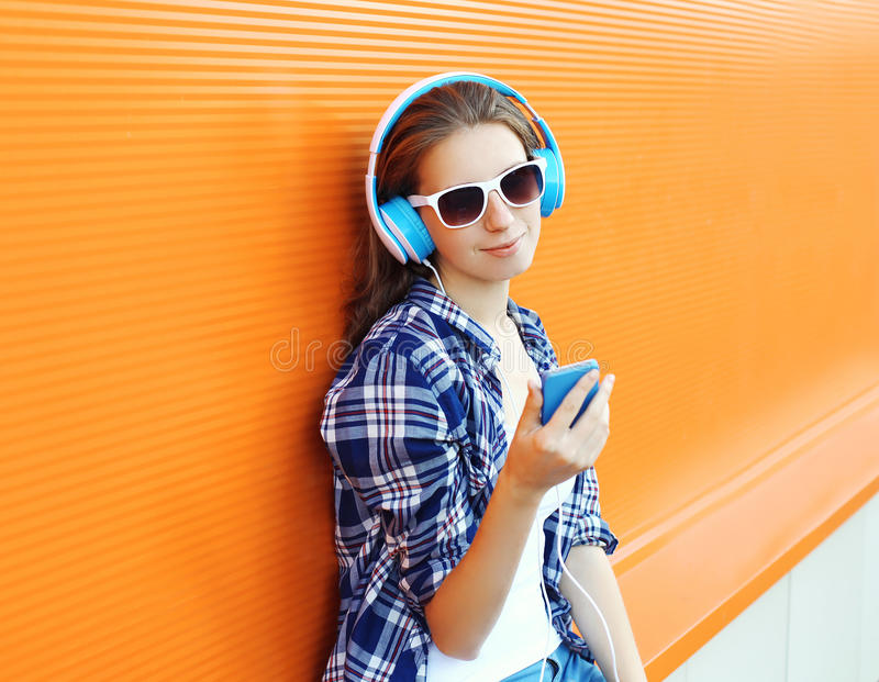 Pretty girl enjoys listen to music in headphones. And using smartphone against the colorful orange wall stock photo