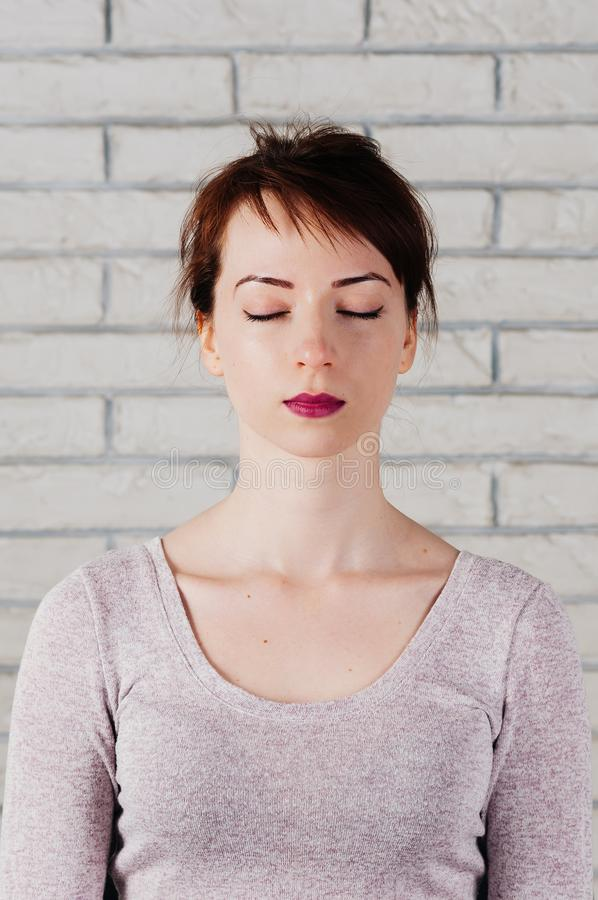 Portrait of attractive girl with eyes closed, peaceful look. A pretty girl with eyes closed as in meditation, peaceful look, with white brick wall in the royalty free stock image