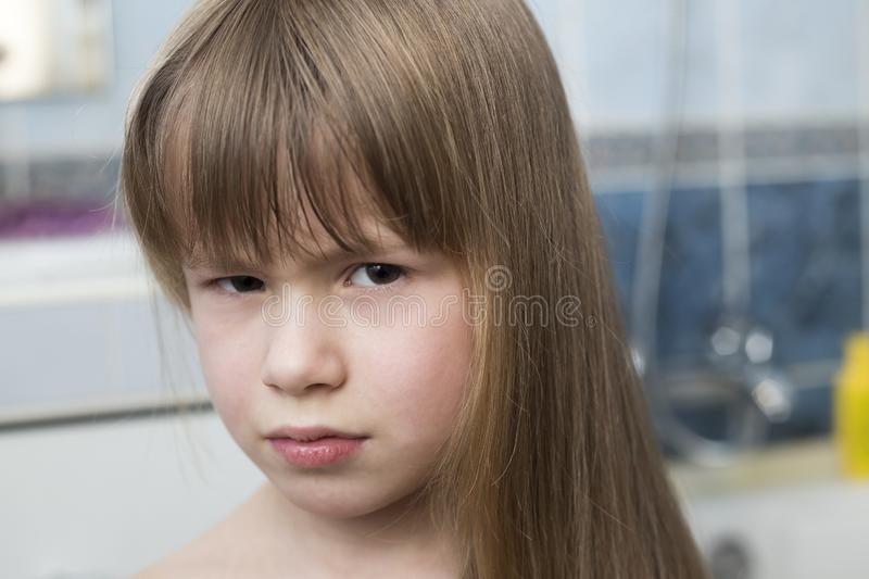 Pretty girl face portrait, child with beautiful eyes and long wet fair hair on blurred background of bathroom royalty free stock image