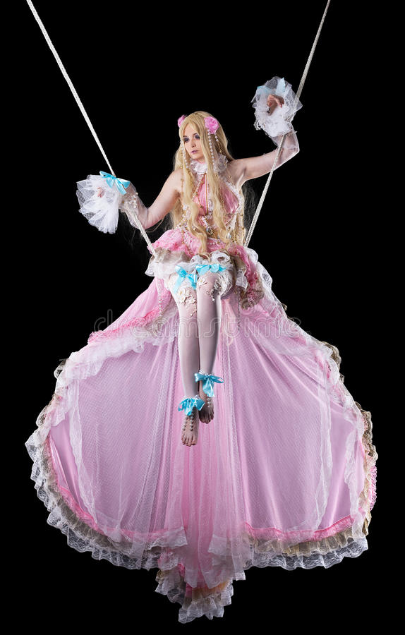 Pretty girl in fary-tale doll costume fly in dark royalty free stock photo