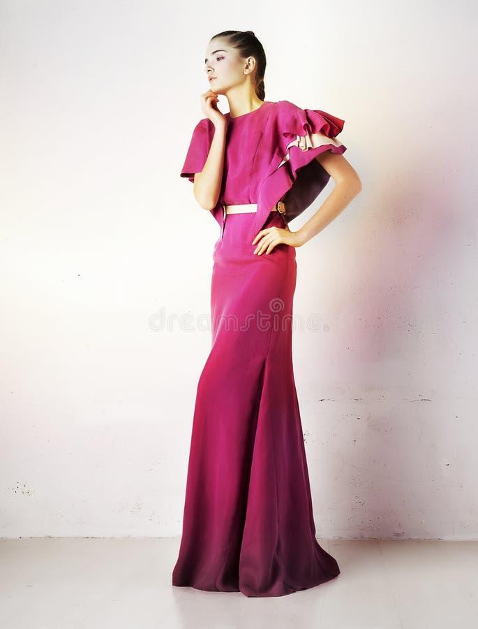Pretty girl in fashion crimson dress studio shot stock photo