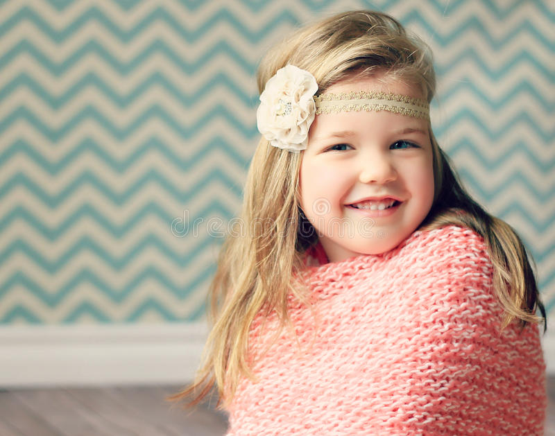 Pretty girl with flower headband and chevron background. Lovely young girl with golden hair and a flower headband poses in front of a teal chevron background stock photography