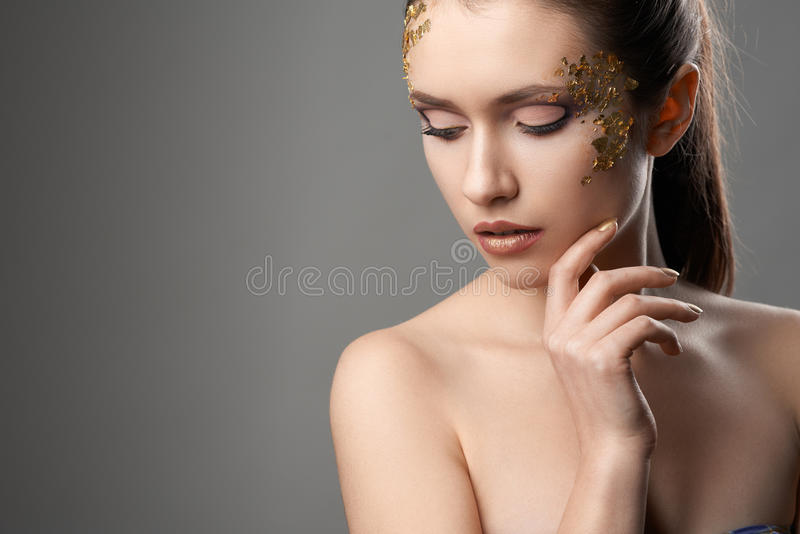 Pretty girl with golden make-up art stock photo