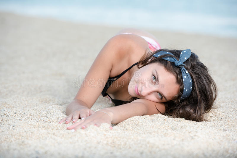 Pretty girl with great body lying on the sand. Pretty girl with great body, long hair and bow headband lying on the sand. Photo taken from head point stock image