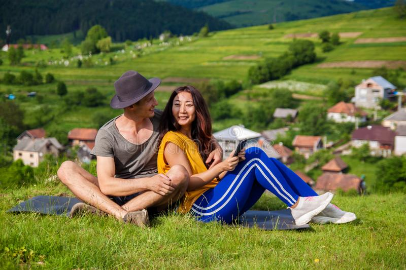 Pretty girl and handsome man joyfully bounding to each other on green grass. stock image