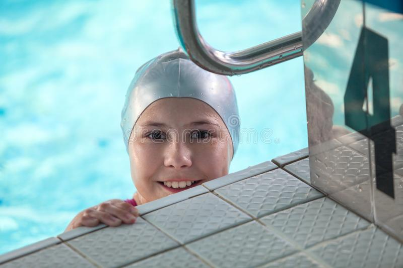 Pretty girl head with grey rubber cap looking at camera from swimming pool and starting block. Pretty girl head with grey rubber cap looking at camera from royalty free stock photo
