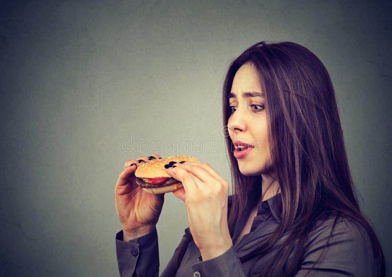 Young woman craving for burger royalty free stock photos