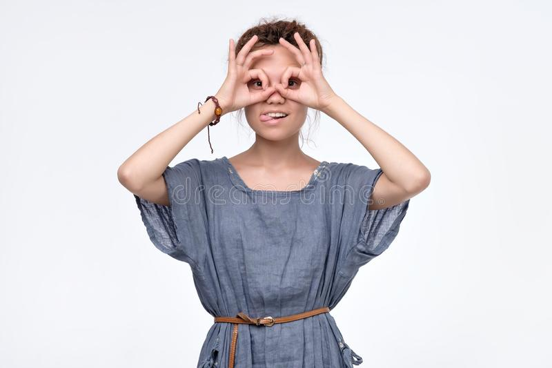 Girl holding fingers near eyes like glasses:. Mask like super hero or owl royalty free stock photo